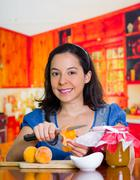 Smiling woman unpeeled a little peach with a big knife, firts step of peach jam Stock Photos