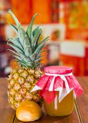Fresh pineapple on a wooden table with a little bread and a glass pot, homemade Stock Photos