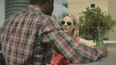 4K Happy mixed ethnicity couple chatting & drinking beer on city rooftop Stock Footage