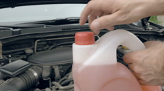 Opening bottle with pink windshield washer fluid - stock footage