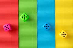 Four dices on colored corrugated paper Stock Photos