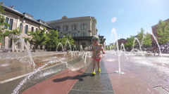 Toddler playing with small fountains on the urban plaza. - stock footage