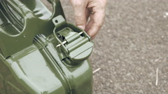 Man opens gas petrol or diesel jerry can with fuel Stock Footage