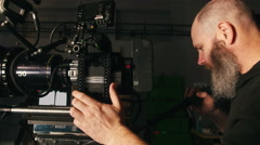 Camera operator waiting for que on pan shot in studio environment Stock Footage