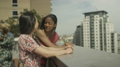 4K Happy female friends chatting & looking at view at rooftop party Stock Footage
