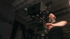 Bearded camera man panning pro rig with large lens in studio - stock footage