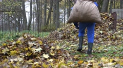 Man carry heavy bag full of leaves on shoulder and dump it on compost pile. 4K Stock Footage