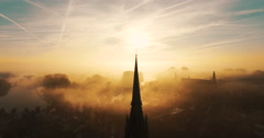 A silhouette of the tower of a church in the early morning with a lot of fog Stock Footage