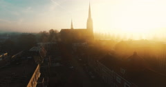 Aerial towards a church covered in fog on an early morning with godrays flying Stock Footage