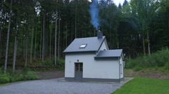 Smoke out of a chalet in the forest and mountains of the Ardennes in Belgium Stock Footage