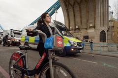 LONDON - ENGLAND 1ST MAY 2016 - Women pushing a Santander hire bike in London Stock Photos
