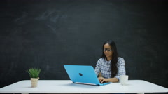 4K Woman working on laptop & looking for inspiration, chalkboard in background - stock footage
