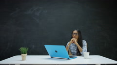 4K Woman working on laptop & looking for inspiration, chalkboard in background Stock Footage