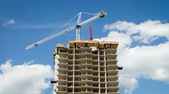 4k Timelapse of a tower crane on top of a building under construction against bl Stock Footage