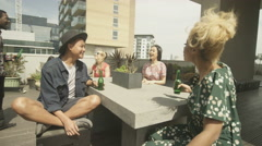 4K Happy group of friends chatting & socializing at city rooftop party Stock Footage