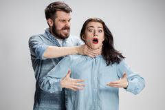 The quarrel men and women. Man strangling a woman on gray background Kuvituskuvat