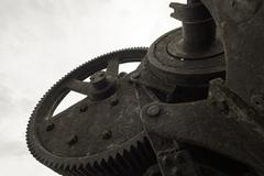 Single black painted cog wheel from an bygone industrial era set against a gr Stock Photos