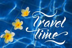 Tropical frangipani flower floating in blue water and words Travel time - stock photo