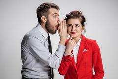 Young man telling gossips to his woman colleague at the office - stock photo