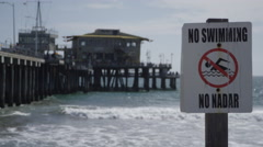 No swimming sign slow motion birds at Santa Monica Pier in Los Angeles Stock Footage
