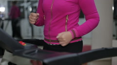 Women in sport running shoes are on a treadmill in a gym Stock Footage
