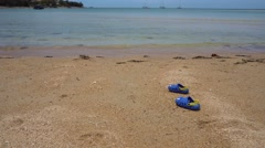 Children shoes left on the beach - stock footage