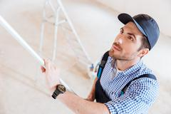 Close-up portrait of a decorator using roller in work - stock photo