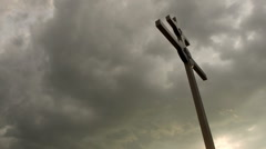 Large cross silhouetted against storm clouds at sunset. - stock footage