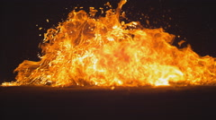 A paper-wrapped molotov cocktail falls to the ground and explodes. Slow motion. Stock Footage