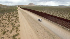 Drone tracking police truck at US border wall Stock Footage