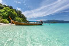 Longtail boat on crystal clear sea at tropical beach Stock Photos
