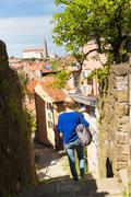 Woman walking on old cobbled street. - stock photo