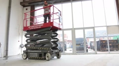 Workman drives hydraulic scissor lifting platform in a warehouse Stock Footage