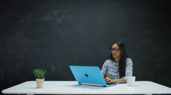 4K Woman working on laptop & looking at chalkboard behind for inspiration Stock Footage