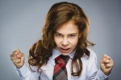 Portrait of angry girl with hands up yelling isolated on gray background - stock photo