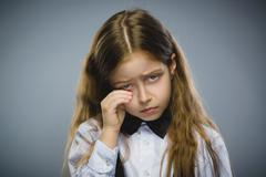 Portrait of offense crying girl isolated on gray background. Negative human Stock Photos