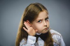 Curious Disappointed girl listens. Closeup portrait child hearing something - stock photo