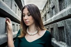 Beautiful brunette woman posing outdoor in abandoned industrial place - stock photo