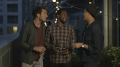 4K Happy male friends drinking & laughing at summer rooftop party Stock Footage
