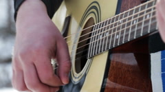 A man playing the acoustic guitar in the outdoors - stock footage