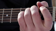 A man playing the acoustic guitar in the outdoors Stock Footage