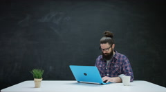4K Man working on laptop & looking for inspiration, chalkboard in background - stock footage