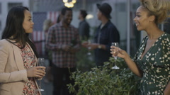 4K Happy attractive friends drinking & socializing at summer rooftop party - stock footage