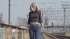 Young pretty shy model walking on the railway and smiling Stock Footage