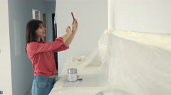 Young woman taking photo of painted wall with cellphone in kitchen at her new ho Stock Footage
