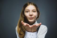 Beautiful Young girl Blowing A Kiss against grey background Stock Photos