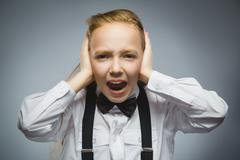 Closeup portrait of screaming girl covering her ears, observing. Hear nothing Stock Photos