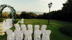 Video of the location of an outdoor wedding. Altar, chairs and garlands. Drone N - stock footage