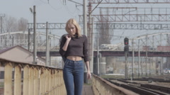 Young pretty shy model walking on the railway and smiling while windy Stock Footage