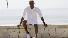 Seated male model wearing shorts and dress shirt - stock footage